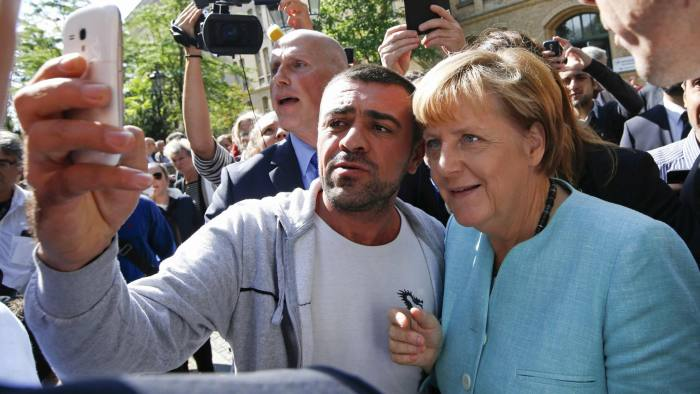 File photo of a migrant taking a selfie with German Chancellor Merkel outside a refugee camp in Berlin...File photo of a migrant taking a selfie with German Chancellor Angela Merkel outside a refugee camp near the Federal Office for Migration and Refugees in Berlin, Germany, September 10, 2015. Time magazine named German Chancellor Angela Merkel its 2015