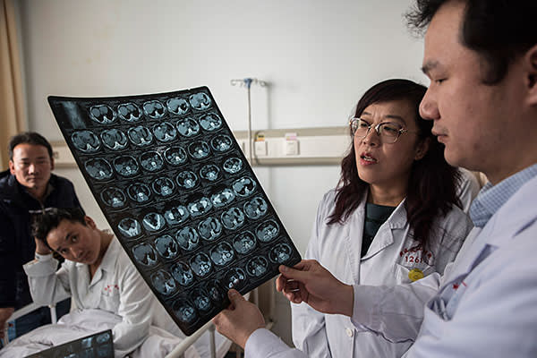 Doctor Shao Yingmei, second right, and a colleague check a scan of the torso of Aga, a Tibetan herder