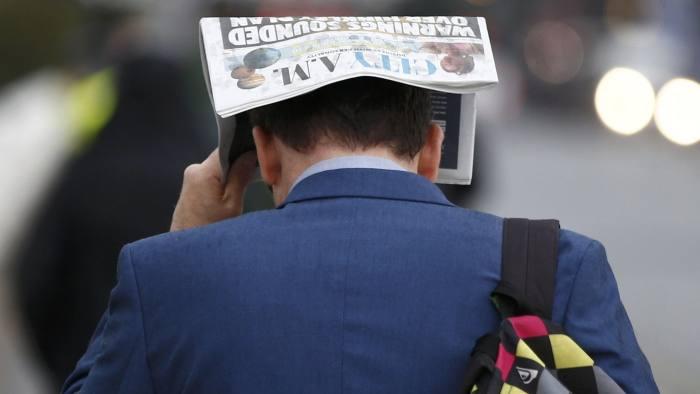 A commuter shelters under a newspaper as he crosses Waterloo bridge during heavy rain in London, Britain September 16, 2016.  REUTERS/Peter Nicholls