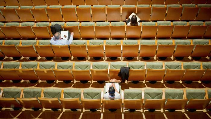 Business people sitting in mostly empty auditorium