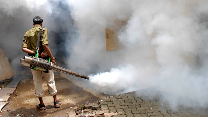 A municipal worker uses an anti-malaria fumigation spray machine in Mumbai