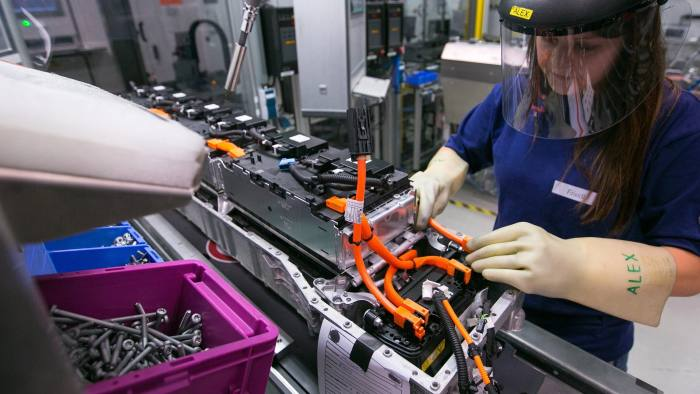 An employee assembles lithium-ion battery modules at the Bayerische Motoren Werke AG (BMW) automobile manufacturing plant in Dingolfing, Germany, on Thursday, Aug. 21, 2014. BMW agreed to spend billions of euros increasing its orders of Samsung SDI Co. batteries as the world's largest maker of luxury cars expands its line of electric vehicles. Photographer: Krisztian Bocsi/Bloomberg
