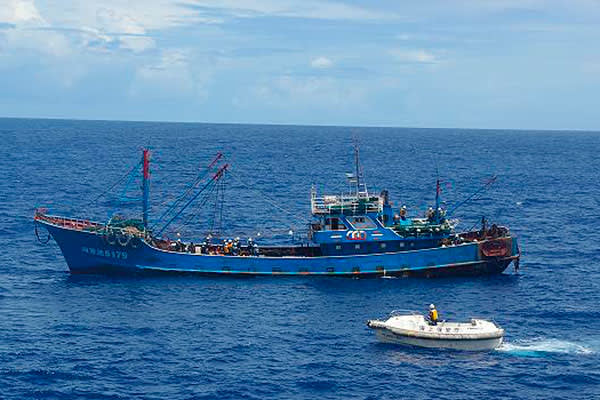 A Chinese fishing boat is inspected by a Japanese vessel