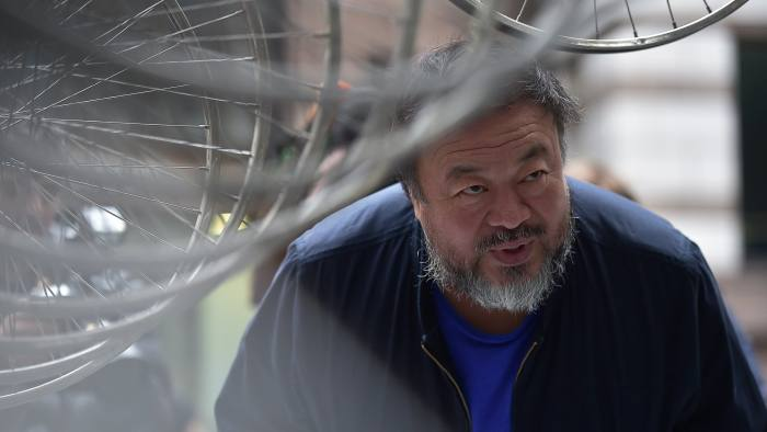 Chinese artist Ai Weiwei looks at his sculpture
