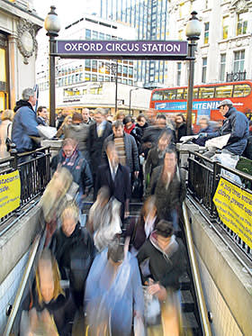A long exposure image showing Tube travelers being handed free afternoon newspapers travelers as they crowd one of the Oxford Circus entrances during the rush hour, in London, Britain