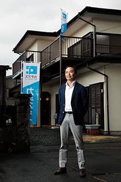 Katsutoshi Arai, the president of Katitas, in front of a renovated house