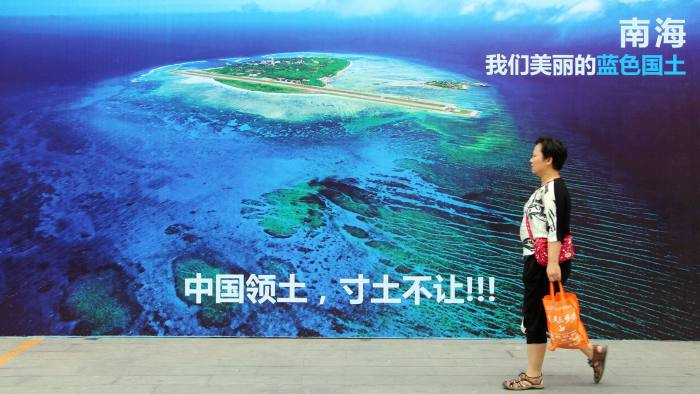 """This photo taken on July 14, 2016 shows a woman walking past a poster of the South China Sea, with the slogan at the bottom """"China's territory, never to yield an inch of our ground"""" on a street in Weifang, east China's Shandong province. China may build mobile nuclear power plants in the South China Sea, state media reported on July 15, days after an international tribunal dismissed Beijing's vast claims in the strategically vital waters. / AFP / STR / China OUT (Photo credit should read STR/AFP/Getty Images)"""