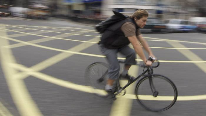 [UNVERIFIED CONTENT] cycle courier speeding over yellow box junction through Piccadilly Circus London in front of the TDK and SANYO advertising.
