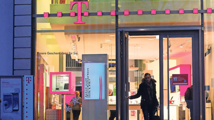 A customer leaves a Deutsche Telekom AG store in Bonn, Germany, on Monday, Dec. 17, 2012