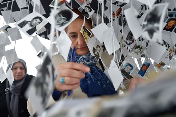 """A women writes a note in the golden book inside the memorial of victims, in front of the International Criminal Tribunal for the former Yugoslavia (ICTY) in The Hague, on November 22, 2017, prior to the verdict in the genocide trial of former Bosnian Serbian commander Ratko Mladic. Dubbed """"The Butcher of Bosnia,"""" Mladic's trial is the last before the ICTY, and the judgement has been long awaited by tens of thousands of victims across the bitterly-divided region, seeking to close a chapter in the brutal 1990s Balkans conflicts. / AFP PHOTO / JOHN THYSJOHN THYS/AFP/Getty Images"""