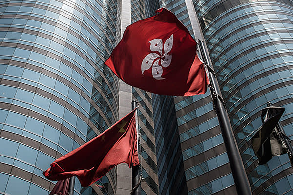 This picture taken on April 16, 2015 shows the Hong Kong flag (centre-R) fluttering next to the Chinese national flag (centre-L) outside the stock exchange building in Hong Kong