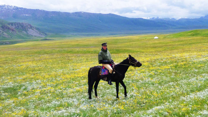 Robin Lane Fox on his stallion 'Kara' ('black') in an edelweiss and buttercup-filled meadow in the Ala-Too mountains, North Tien Shan range, Kyrgyzstan