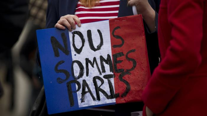 "A woman holds a French flag colored placard with French translating as ""we are Paris"" whilst attending a vigil for victims of the deadly Paris attacks, in Trafalgar Square, London, Saturday, Nov. 14, 2015. French President Francois Hollande said more than 120 people died Friday night in shootings at Paris cafes, suicide bombings near France's national stadium and a hostage-taking slaughter inside a concert hall. (AP Photo/Matt Dunham)"