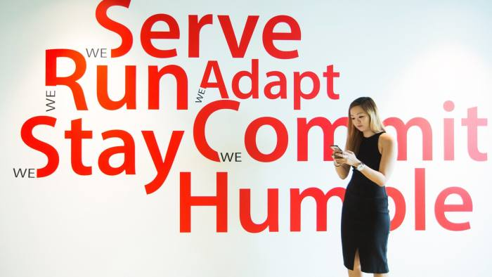An employee uses a smartphone while standing in front of signage at the Garena Interactive Holding Ltd. headquarters in Singapore, on Thursday, Aug. 25, 2016. Garena, a gaming and e-commerce empire that is now Southeast Asia's largest startup, is a Singapore-based company that's valued at more than $3.75 billion. Photographer: Nicky Loh/Bloomberg
