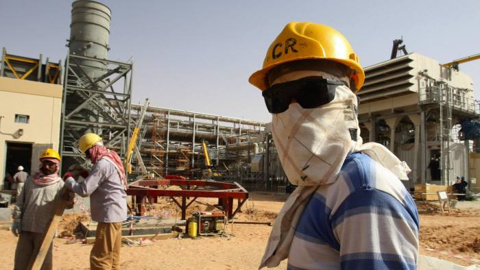 A worker looks at journalists during a media tour of the Khurais oilfield, about 160 km (99 miles) from Riyadh, June 23, 2008. State oil giant Saudi Aramco is adamant the biggest new field in its plan to raise oil capacity will arrive bang on schedule in June next year. REUTERS/Ali Jarekji (SAUDI ARABIA)