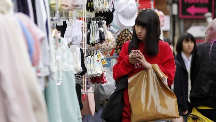A woman uses her mobile device outside a clothing store on Takeshita Street in the Harajuku district of Tokyo, Japan, on Monday, March 23, 2015. Bank of Japan Governor Haruhiko Kuroda last week prepared the public for the potential return of falling prices, while expressing confidence any such declines would be temporary as policy makers keep up their battle to foster inflation. Photographer: Kiyoshi Ota/Bloomberg