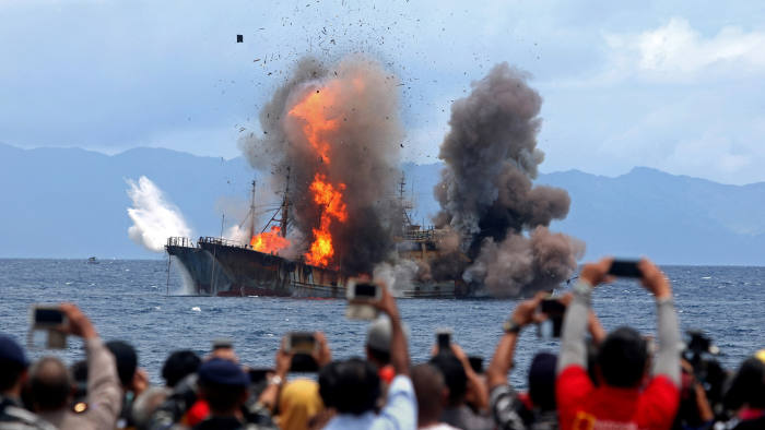 People take pictures of a burning ship as the government destroyed foreign boats that had been caught illegally fishing in Indonesia waters, at Morela village in Ambon island, April 1, 2017 in this photo taken by Antara Foto. Picture taken April 1, 2017. Antara Foto/Izaac Mulyawan/via REUTERS ATTENTION EDITORS - THIS IMAGE WAS PROVIDED BY A THIRD PARTY. FOR EDITORIAL USE ONLY. MANDATORY CREDIT. INDONESIA OUT. TPX IMAGES OF THE DAY
