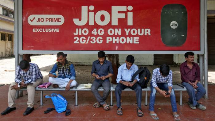 Commuters use their mobile phones as they wait at a bus stop with an advertisement of Reliance Industries' Jio telecoms unit, in Mumbai, India July 10, 2017. REUTERS/Shailesh Andrade