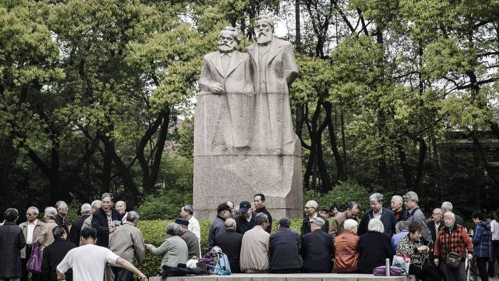 People chat in front of a statue of Karl Marx and Friedrich Engels at Fuxing Park in Shanghai, China, on Sunday, April 10, 2016. China's economy stabilized last quarter and gathered pace in March as a surge in new credit helped the property sector rebound while raising fresh question marks over the sustainability of the debt-fueled expansion. Photographer: Qilai Shen/Bloomberg
