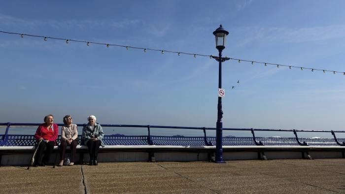 Elderly ladies sit in the spring sunshine on Eastbourne Pier in Eastbourne, U.K., on Tuesday, April 1, 2014. Pensioners and savers have seen returns on their money shrink since the financial crisis drove interest rates to a record low. Photographer: Chris Ratcliffe/Bloomberg