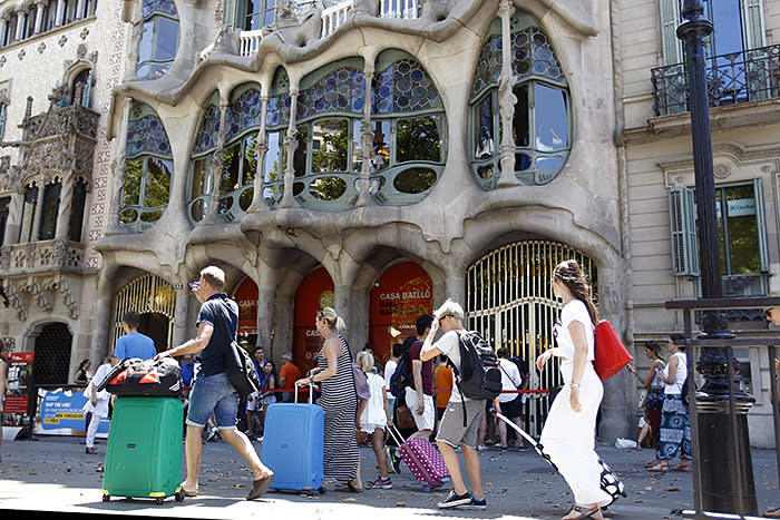 Tourists pull their suitcases in front of Spanish architect Gaudi's Casa Batllo in Barcelona on June 28, 2015
