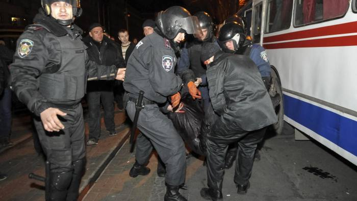 Police officers carry a wounded participant of an anti-war rally during clashes with pro-Russia demonstrators in Donetsk on March 13 2014