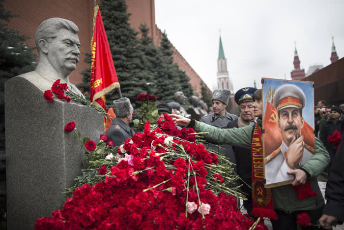A woman holding a portrait of Stalin places flowers near the monument signifying Joseph Stalin's grave near the Kremlin wall marking the anniversary of Stalin's birth in Moscow's Red Square, Russia, Thursday, Dec. 21, 2017. (AP Photo/Alexander Zemlianichenko)
