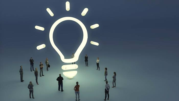 Group of people gathering around a glowing lightbulb symbol