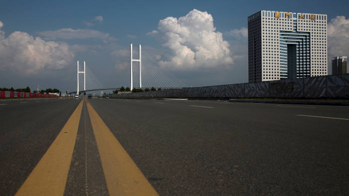 An empty street runs in front of the unfinished New Yalu River bridge (L) and the empty Chinese customs building in Dandong, Liaoning province, China, September 11, 2016. The bridge was designed connect China's Dandong New Zone and North Korea's Sinuiju. REUTERS/Thomas Peter - RTSN792