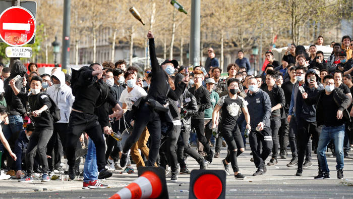 Prostesters throw bottles to French CRS riot police after a ceremony in memory of 56-year-old Shaoyao Liu, who was shot dead by police at his Paris home last Sunday, in Paris, France April 2, 2017. REUTERS/Charles Platiau TPX IMAGES OF THE DAY