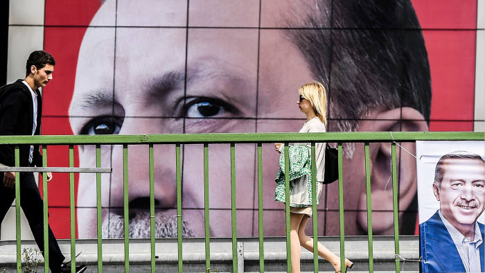 People walk in front of a giant poster of Turkish President Recet Tayyip Erdogan on April 6, 2017 in Istanbul, 10 days ahead of the referendum on whether to change the current parliamentary system into an executive presidency. / AFP PHOTO / BULENT KILIC (Photo credit should read BULENT KILIC/AFP/Getty Images)