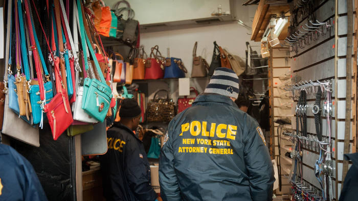Power of enforcement: police officers removing counterfeit goods from a shop in New York