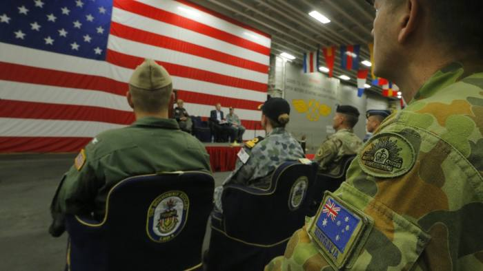 epa06055344 A member of the Australian Army sits in the audience alongside a US flag as the backdrop of a ceremony marking the start of Talisman Saber 2017, a biennial joint military exercise between the United States and Australia aboard the USS Bonhomme Richard amphibious assault ship on the the Pacific Ocean off the coast of Sydney, New South Wales, Australia, 29 June 2017. EPA/JASON REED / POOL AUSTRALIA AND NEW ZEALAND OUT