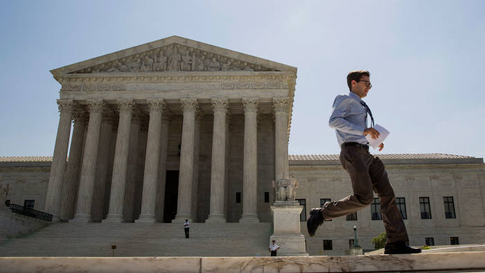 An intern runs an opinion to colleagues in front of the U.S. Supreme Court in Washington, D.C., U.S., on Monday, June 22, 2015.