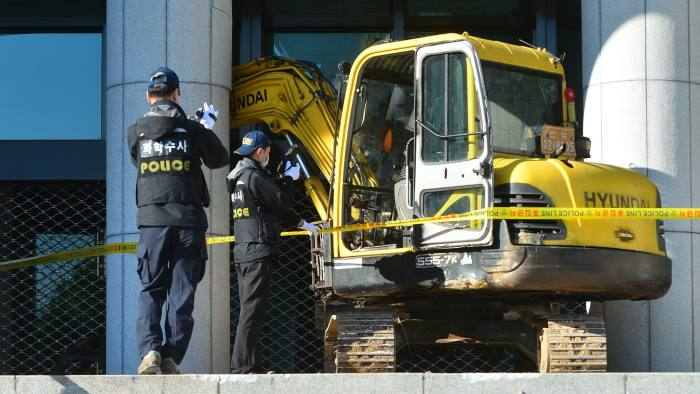 Policemen examine a heavy construction excavator that an unidentified men used to smash the front entrance of the Supreme Prosecutors' Office building in Seoul, South Korea, November 1, 2016. Min Kyeong-soek/News1 via REUTERS ATTENTION EDITORS - THIS IMAGE HAS BEEN SUPPLIED BY A THIRD PARTY. SOUTH KOREA OUT. FOR EDITORIAL USE ONLY. NO RESALES. NO ARCHIVE.