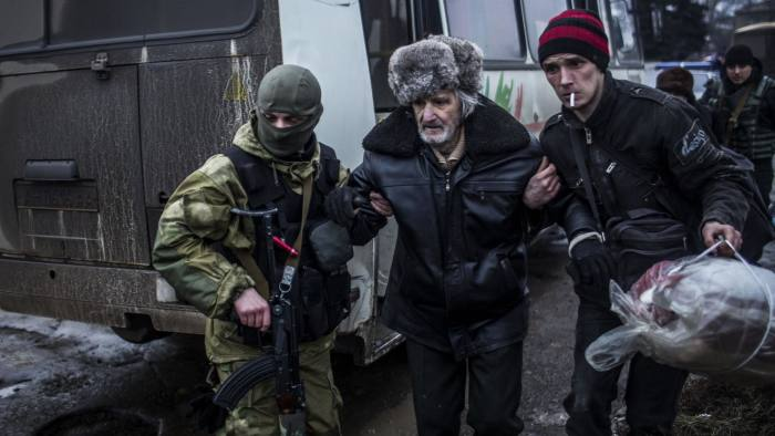 An elderly Ukrainian man is helped by a Ukrainian Army soldier and a citizen during a evacuation of civilians in Debaltseve, in the Donetsk region, on February 3, 2015 At least 19 civilians and five government troops were killed over the previous 24 hours as fierce clashes raged between pro-Russian separatists and Ukraine's outgunned forces in the east of the country, insurgent and government officials said.  AFP PHOTO / MANU BRABO        (Photo credit should read MANU BRABO/AFP/Getty Images)