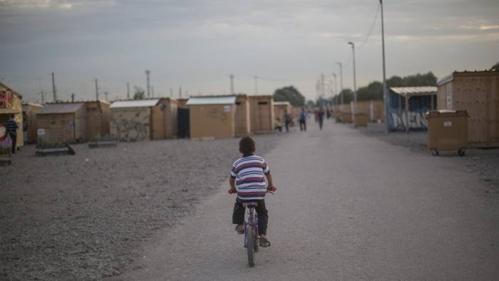 A boy cycles through the Grande-Synthe camp in Dunkirk