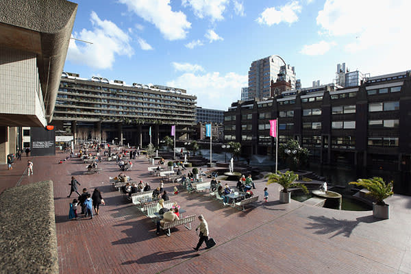 People sit outside The Barbican arts and residential centre in London