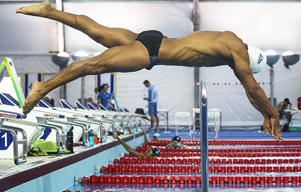 Olympic refugee team swimmer Rami Anis dives while training at the Olympic Aquatics Stadium
