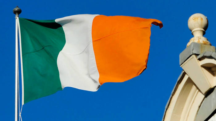 The Irish national flag flies from a flagpole above a building in Dublin, Ireland.