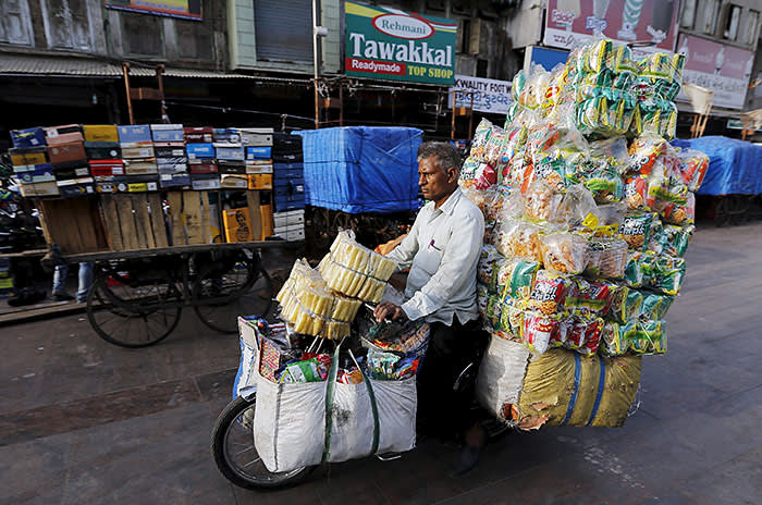 A vendor transports food packets on his moped during morning in the western Indian city of Ahmedabad April 9, 2015. REUTERS/Amit Dave