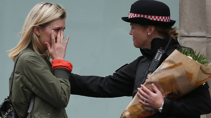 TOPSHOT - A woman reacts after asking a Police officer to lay flowers near London Bridge in London on June 4, 2017, as a tribute to the victims of the June 3 terror attack. Seven people were killed in a terror attack on Saturday by three assailants on London Bridge and in the bustling Borough Market nightlife district, the chief of London's police force said on Sunday. / AFP PHOTO / Daniel LEAL-OLIVASDANIEL LEAL-OLIVAS/AFP/Getty Images