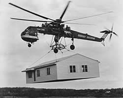 A prefab home being lifted by helicopter in 1970