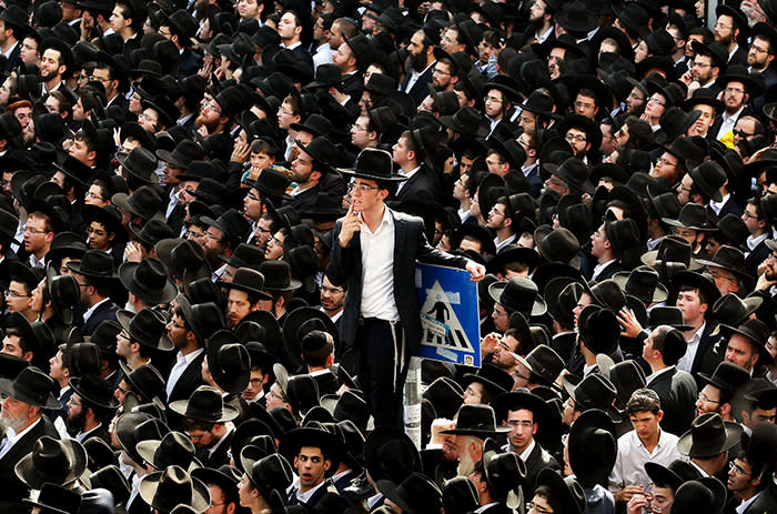 Jewish men gather to watch the funeral of leading spiritual authority for ultra-Orthodox Jews in Israel and around the world, Rabbi Aaron Yehuda Leib Shteinman, in the central Israeli city of Bnei Brak on December 12, 2017. Shteinman, who also wielded heavy influence on Israeli ultra-Orthodox political parties, had been hospitalised at the Mayanei Hayeshua medical centre three weeks ago over breathing problems. He died aged 104, the hospital said. / AFP PHOTO / GIL COHEN-MAGENGIL COHEN-MAGEN/AFP/Getty Images