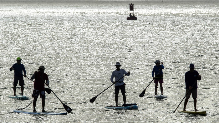 Paddle boarders make their way around Dana Point Harbor as the sun shines through partly cloudy skies in Dana Point, Calif., Tuesday morning, Feb. 14, 2017. (Mark Rightmire/The Orange County Register via AP)
