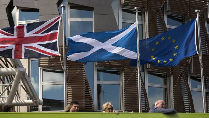 A Scottish Saltire (C) flies between a Union flag (L) and a European Union (EU) flag in front of the Scottish Parliament building in Edinburgh, Scotland on June 27, 2016. British leaders battled to calm markets and the country Monday after its shock vote to leave the EU, while insisting London would be not rushed into a quick divorce. Britain's historic decision to be the first country to leave the 28-nation bloc has fuelled fears of a break-up of the United Kingdom with Scotland eyeing a new independence poll, and created turmoil in the opposition Labour party where leader Jeremy Corbyn is battling an all-out revolt. / AFP / OLI SCARFF (Photo credit should read OLI SCARFF/AFP/Getty Images)