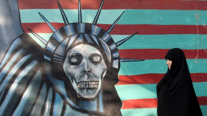 """An Iranian woman walks past a mural on the wall of the former US embassy in the Iranian capital Tehran on November 9, 2016. Iran's President Hassan Rouhani said there was """"no possibility"""" of its nuclear deal with world powers being overturned by US president-elect Donald Trump despite his threat to rip it up.   / AFP / ATTA KENARE        (Photo credit should read ATTA KENARE/AFP/Getty Images)"""