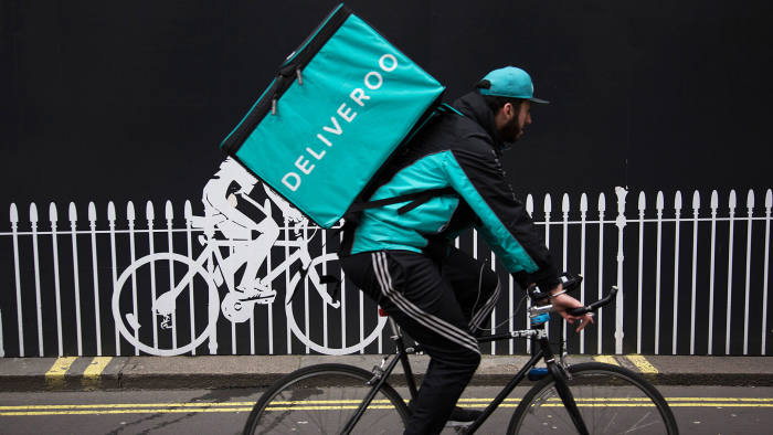 Deliveroo cycle courier with his large back box interacts with a stencilled cyclist while out delivering in London, England, United Kingdom