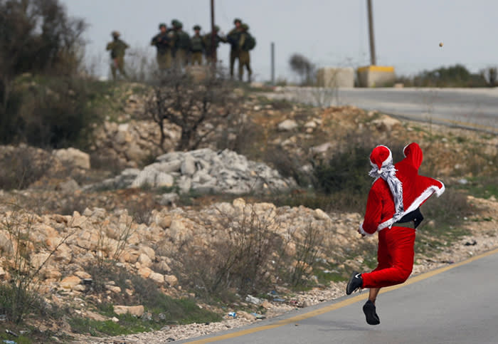 A Palestinian demonstrator dressed as Santa Claus hurls stones towards Israeli troops during clashes at a protest against U.S. President Donald Trump's decision to recognize Jerusalem as the capital of Israel, near the West Bank city of Ramallah December 19, 2017. REUTERS/Mohamad Torokman