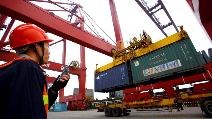 This photo taken on January 8, 2012 shows a worker operating hoists to unload containers at the Kaikou port, in south China's Hainan province. China's trade surplus shrank in 2011 as import and export growth slowed sharply, official data showed on January 10 , after domestic tightening measures and global economic turmoil hit consumption. CHINA OUT AFP PHOTO